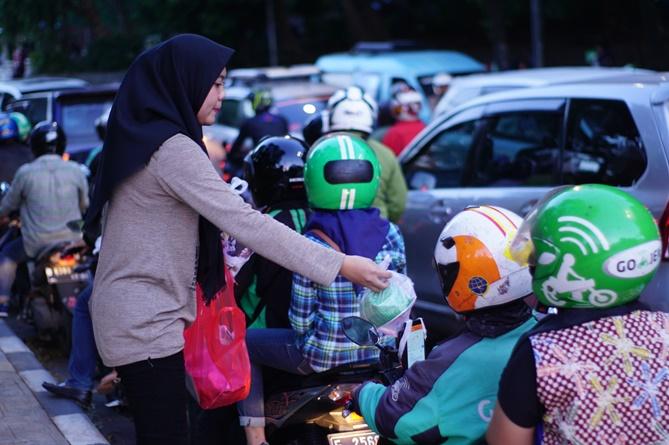 Petugas PPMB membagikan takjil kepada pengguna jalan di Pejaten, Jumat (24/5)