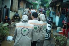 Rombongan FIKES UNAS berjalan menuju rumah korban banjir Faiz mahasiswa UNAS