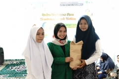 "Mahasiswa FIKES UNAS Asya Azzahra Z (tengah) memberika hadiah kepada anak yatim (kiri dan kanan) pada acara buka bersama dan santunan anak yatim ""Ramadhan penuh berkah untuk kita yang membutuhkan' di gedung pascasarjana menara 2 UNAS lantai 2"