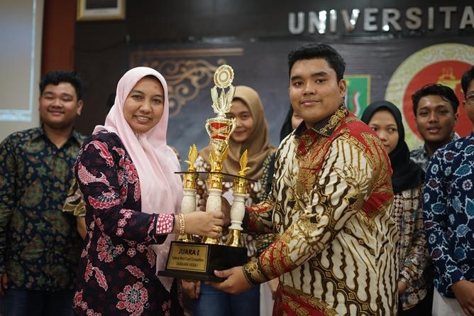 Wakil Dekan Fakultas Hukum Ummu Salamah, S.Ag., M.A. (kiri) memberikan hadiah kepada pemenang moot court (kanan)