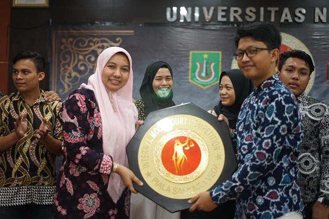 Wakil Dekan Fakultas Hukum Ummu Salamah, S.Ag., M.A. (kiri) memberikan piala bergilir kepada pemenang moot court (kanan)
