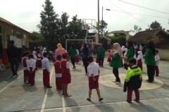 Dosen dan mahasiswa sedang bermain dengan anak-anak sekolah dasar