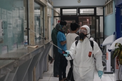 Petugas (putih) melakukan penyemprotan di ruang biro/badan UNAS didampingi petugas pengawas kampus pada Minggu (22/3)