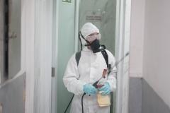 Petugas melakukan penyemprotan disinfektan di ruang biro/badan UNAS didampingi petugas pengawas kampus pada Minggu (22/3)