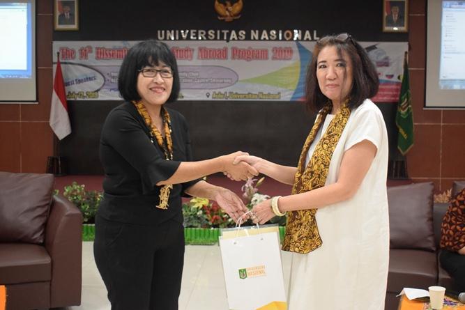 pemberian cenderamata dari Kepala Divisi Kerjasama Luar Negeri KKI Unas, Dra. M.A. Inez Sapteno kepada Manager of AECC Global Jakarta, Yonela Tananda