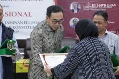 Pemberian cinderamata kepada narasumber diberikan oleh Wakil Rektor Bidang Penelitian dan Pengabdian pada MasyarakatProf. Dr. Ernawati Sinaga, M.S., Apt.