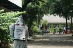 Petugas melakukan penyemprotan disinfektan di lingkungan Universitas Nasional pada Sabtu (21/3)