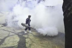 Proses pengasapan fogging di area sekolah pascasarjana Universitas Nasional