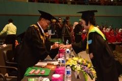 Rektor sedang menyematkan cincin kepada mahasiswa & mahasiswi terbaik