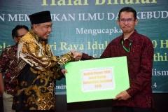 Ketua Pengurus Yayasan Memajukan Ilmu dan Kebudayaan (YMIK) Dr. H. Ramlan Siregar, M.Si. memberikan hadiah berupa umroh kepada staff UNAS