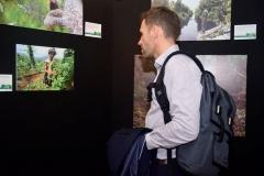 USAID Environment Office Director Matthew Burton melihat pameran foto pada peringatan hari hutan internasional di Selasar lantai 1 Universitas Nasional, Senin (26/3)