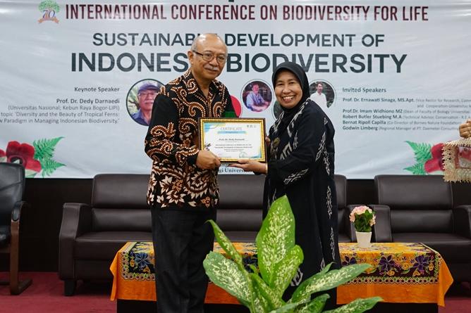 """Peneliti Lembaga Ilmu Pengetahuan Indonesia (LIPI) Prof. Dr. Dedi Darnaedi (kiri) menerima sertifikat sebagai keynote speaker  yang diberikan langsung oleh Wakil Rektor Bidang Penelitian dan Pengabdian pada MasyarakatProf. Dr. Ernawati Sinaga, M.S., Apt. (kanan) pada acara International Conference On Biodiversity For Life dengan tema """"Sustainable Development Of Indonesia Biodiversity"""", di Auditorium Blok 1 lantai 4 Universitas Nasional, Senin (20/10)"""