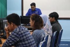 Instruktur sedang menjelaskan tentang dasar desain grafis di depan peserta pelatihan.