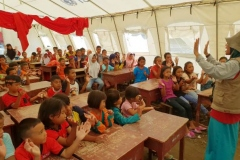 relawan sedang memberikan materi kepada anak-anak korban bencana