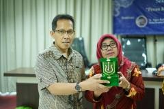 Ketua Program StudiMagister Ilmu Admimistrasi Publik Drs. Rusman Ghazali, M.Si., Ph.D. (kiri) memberikan plakat kepada narasumber
