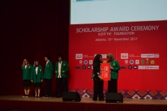 mahasiswa unas naik ke atas panggung untuk menerima penghargaan beasiswa