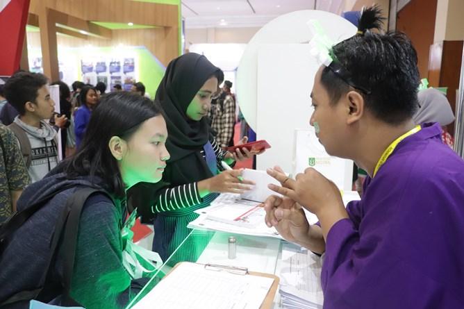 pengunjung sedang bertanya-tanya ke stand UNAS