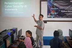 Instruktur sedang menerangkan materi tentang perkembangan cyber security di depan peserta
