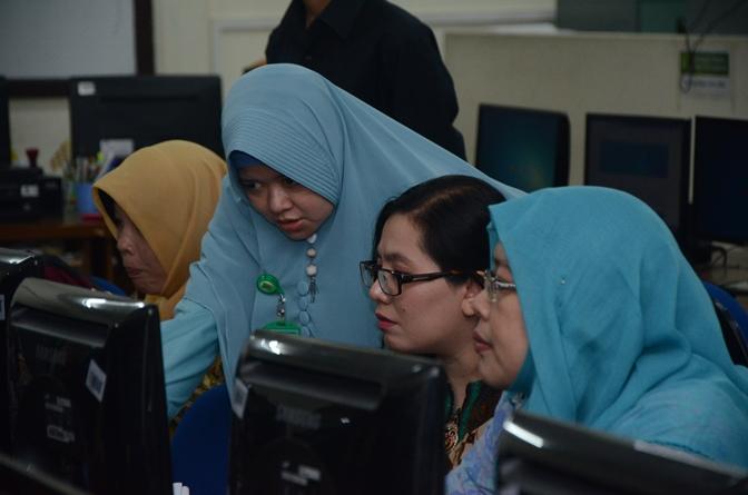 Peserta pelatihan pengelolaan e-learning  (kanan) menjajal aplikasi pembelajaran berbasis online dibantu oleh instruktur (kanan)