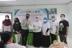 Pemberian cenderamata dari FIKES Unas kepada WOCARE Indonesia.