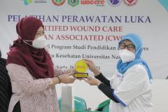 Pemberian cenderamata dari WOCARE Indonesia kepada FIKES Unas.