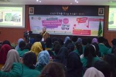 instruktur sedang menjelaskan materi kepada mahasiswa baru di Aula UNAS