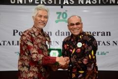 Rektor Universitas Nasional Dr.Drs. El Amry Bermawi Putera, M.A (kanan) memberikan cinderamata kepada Prof. Dr. Drs. Endang Sukara, APU (kiri) sebagai narasumber pada acara dies natalis Unas ke 70 di auditorium blok 1 lantai 4 Unas, Selasa (15/10)