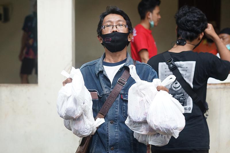 Karyawan UNAS menerima daging hewan qurban di area Masjid Sutan Takdir Alisjahbana, Selasa 20 Juli 2021