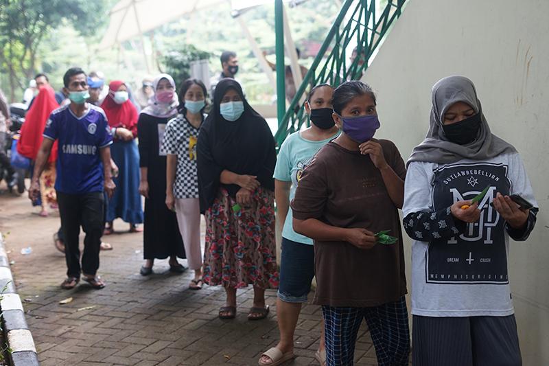 Suasana saat masyarakat mengantre pengambilan daging hewan qurban di area Masjid Sutan Takdir Alisjahbana, Selasa 20 Juli 2021