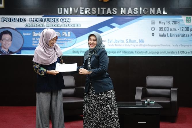 Moderator  Evi Jovita S.Hum., M.A. menerima cinderamata yang diberikan oleh Dosen fakultas bahasa dan sastra Siti Tuti Alawiyah S.S., M.Hum. pada acara public lecture di aula blok 1 lantai 4 UNAS, Kamis (16/5)