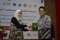 Dr. Retno Widowati, M.Si.- Dekan Fakultas Ilmu Kesehatan Universitas Nasional, memberikan penghargaan kepada Pungkas Bajuri Ali.,Sp.MS.,P.hD Direktur Kesehatan dan Gizi Badan Perencanaan dan Pembangunan Nasional (BAPPENAS) sebagai pembicara pada acara Internasional Confrence On Health Sciences (ICHS) di Jakarta,(14/3)