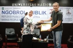 """Wakil Dekan Fakultas Hukum Ummu Salamah, S.Ag., M.A. (kiri) memberikan sertifikat kepada Politisi PSI-Tim TKN Jokowi-Ma'aruf Amin Rian Ernest (kanan) sebagai pembicara pada Seminar Nasional Fakultas Hukum """"Ngobrol Publik """"Refleksi Pemilu Serentak 2019 & Narasi People Power"""" di Auditorium Blok 1 lantai 4 UNAS, Senin (21/5)"""