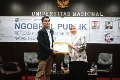 Wakil Dekan Fakultas Hukum Ummu Salamah, S.Ag., M.A. (kanan) memberikan sertifikat kepada Direktur Eksekutif Gajah Mada Analitika Herman Digantara (kiri) sebagai moderator