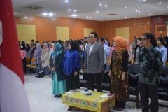 para dosen dan peserta seminar sedang menyanyikan lagu indonesia raya