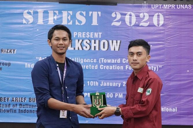 Penyerahan cinderamata kepada narasumber Talkshow AI Research Group Lead at Nodeflux Muhammad Rizky Munggaran (kiri) diberikan oleh Ketua Himpunan Mahasiswa Sistem Informasi Alwi Saipul Zainan (kanan)