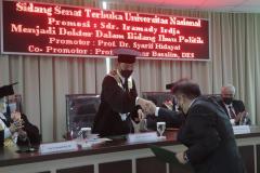 Penyerahan keputusan kelulusan oleh Prof. Dr. Syarif Hidayat pada Sidang Promosi Doktor Program Ilmu Politik  Sekolah Pascasarjana UNAS atas nama Iramady Irdja pada Kamis, 23 September 2021