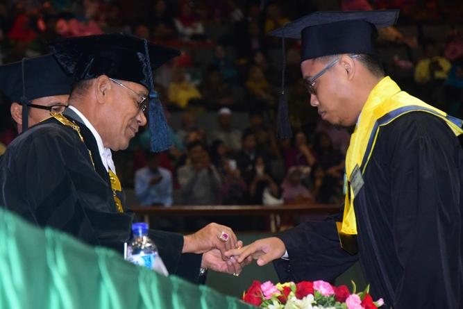 Rektor UNAS saat menyematkan cincin emas kepada wisudawan terbaik di Fakultas