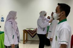 Pemasangan name tag oleh Kepala Prodi Pendidikan Profesi Ners, Ns. Naziyah, S.Kep., M.Kep. kepada perwakilan mahasiswa