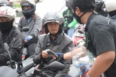 Pengendara motor mendapatkan masker dari petugas Unas