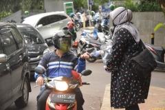 Petugas Unas sedang membagikan masker ke pengguna jalan