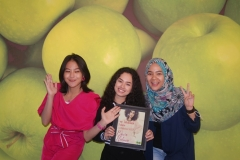 Crew UNAS Radio, Fafau (kiri) dan Sekar (kanan) saat memberikan piagam kenang kenangan kepada penyanyi pendatang baru, Wizzy (tengah) di Lab Radio Bambu Kuning