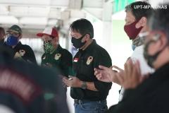 Anggota Universitas Nasional Biker's Community (UNBC) memanjatkan doa sebelum pembagian bantuan dilakukan