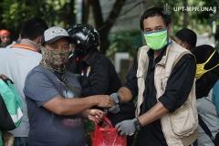 Anggota Universitas Nasional Biker's Community (UNBC) (kanan) memberikan bantuan makanan gratis kepada buruh kerja harian (kiri) di Menara Unas sekolah pascasarjana Rabu, 22 April 2020