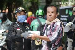 Anggota Universitas Nasional Biker's Community (UNBC) (kiri) memberikan bantuan makanan gratis kepada buruh kerja harian (kanan) di Menara Unas sekolah pascasarjana Rabu, 22 April 2020