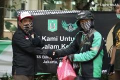 Anggota Universitas Nasional Biker's Community (UNBC) (kiri) memberikan bantuan makanan gratis kepada driver online (kanan) di Menara Unas sekolah pascasarjana Rabu, 22 April 2020