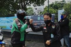 Anggota Universitas Nasional Biker's Community (UNBC) (kanan) memberikan bantuan makanan gratis kepada driver online (kiri) di kampus Unas Pejaten. Rabu, 22 April 2020