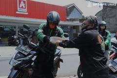 Wakil Kepala BAU Saptomo Setiawan, S.P., M.M. (Kanan) memberikan bantuan makanan gratis kepada driver online (kiri) di kampus Unas Pejaten. Rabu, 22 April 2020
