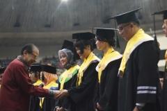 Drs. Drs. Anak Agung Gede Ngurah Puspayoga (Menteri Koperasi dan Usaha Kecil dan Menengah Indonesia) memberikan selamat kepada wisudawan terbaik