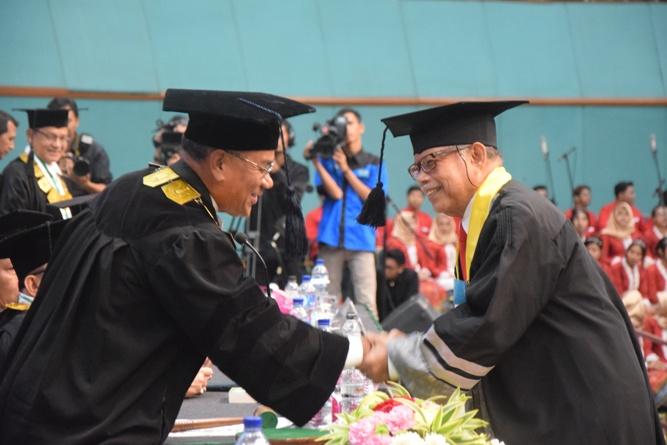 rektor unas berjabat tangan dengan wisudawan