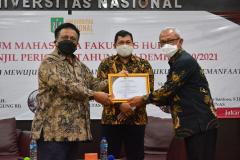 Pemberian sertifikat kepada narasumber, Hakim Agung Mahmakah Agung RI, Dr. Pri Pambudi Teguh, S.H., M.H (kanan), dari Dekan Fakultas Hukum, Prof. Dr. Basuki Rekso Wibowo, S.H., M.S. (kiri).